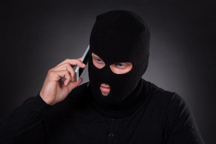 Мошенник в маске с телефоном