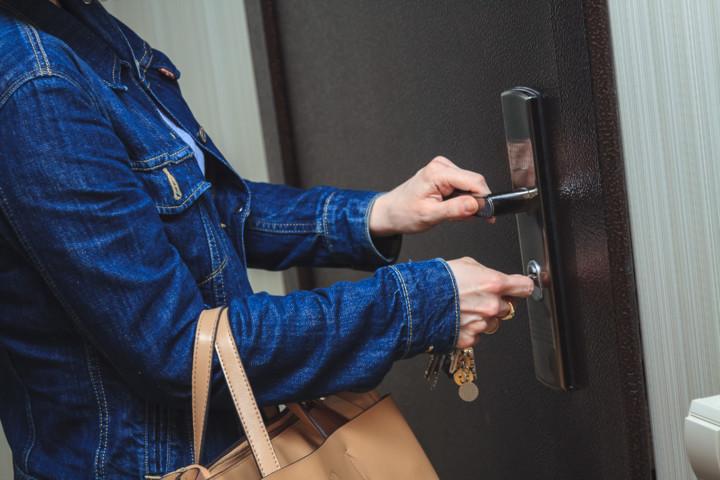 Женщина открывает ключом дверь