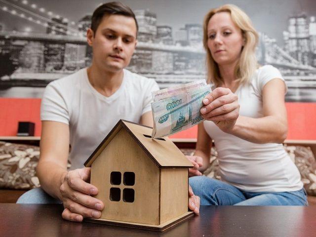 Мужчина и женщина бросают деньги в копилку