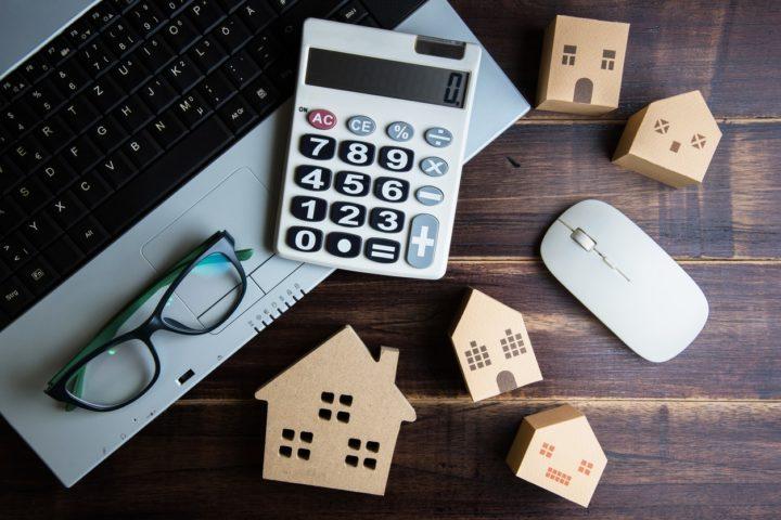 Калькулятор, ноутбук и маленькие домики