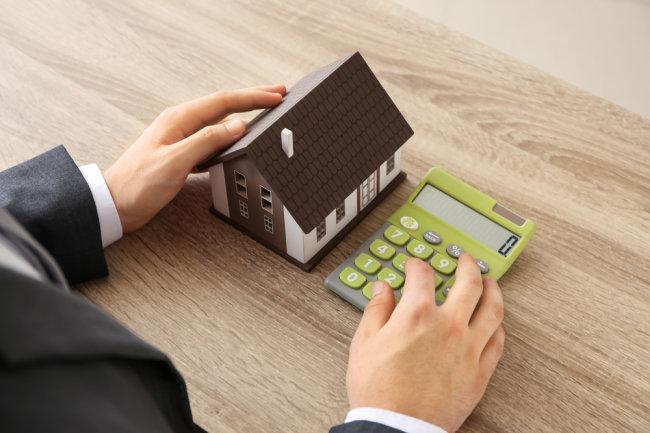 Мужчина держит калькулятор и макет дома