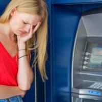 Грустная женщина возле банкомата