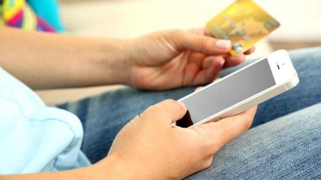 Мужчина держит телефон и банковскую карточку