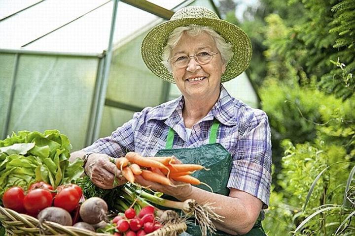 Женщина показывает выращенные овощи