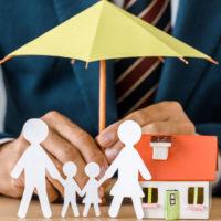 Мужчина держит зонтик над фигурками семьи и дома