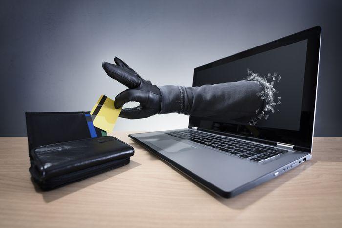 Рука мошенника ворует карту из монитора