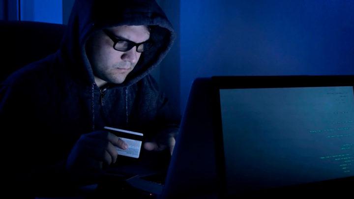 Хакер сидит за компьютером с картой