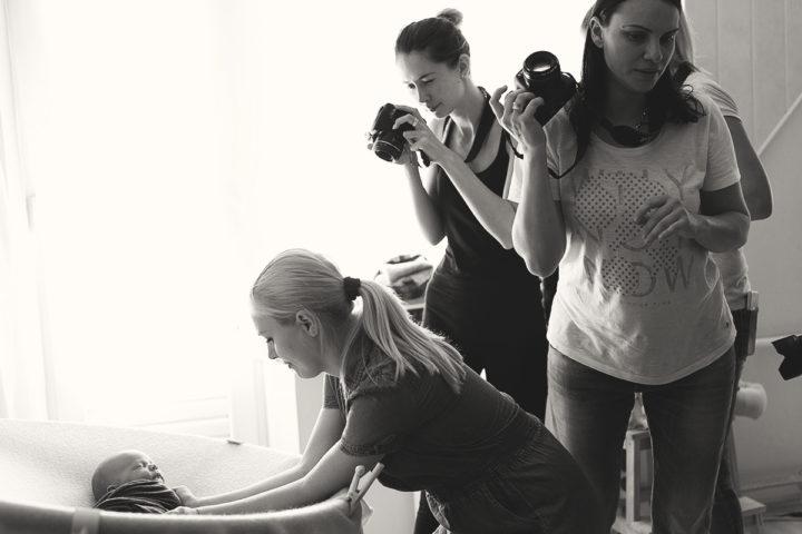 Фотографы подготавливают младенца к съемке