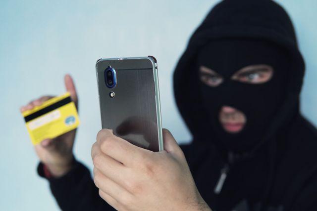 Мошенник с телефоном и карточкой