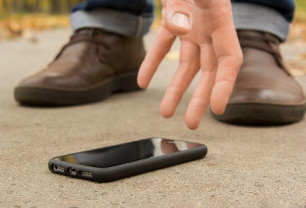 Мужчина поднимает с земли телефон