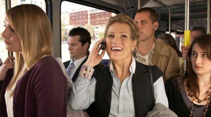 Женщина говорит по телефону в автобусе