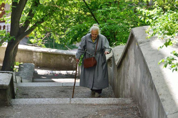 Пожилая женщина идет по ступенькам