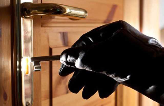 Вор вставляет ключ в замочную скважину