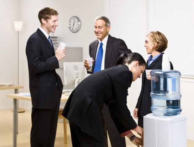Работники в офисе пьют воду из кулера