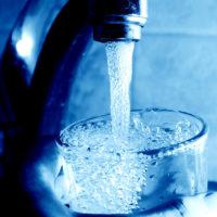 Из крана течет вода в стакан