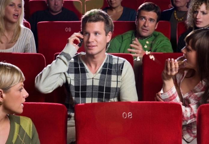 Парень говорит по телефону в кинотеатре