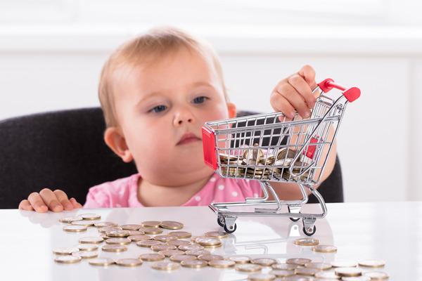Ребенок складывает монеты в тележку