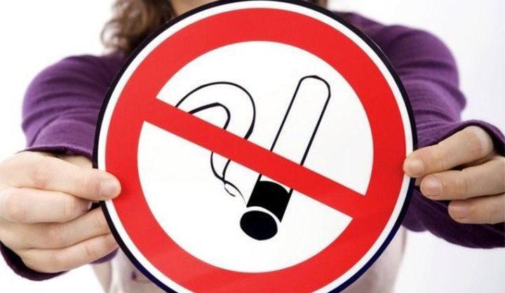 Девушка держит знак, запрещающий курить