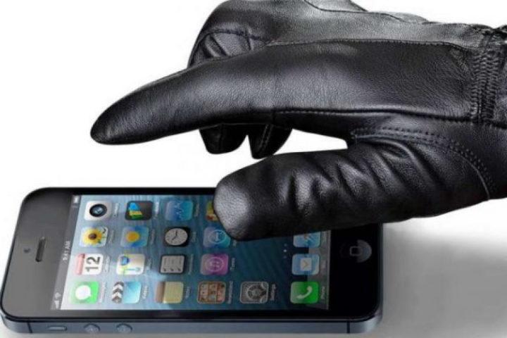Рука в перчатке берет смартфон
