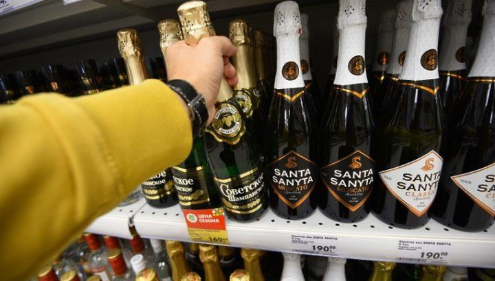 Мужчина берет шампанское с полки
