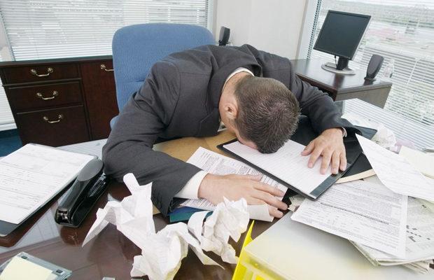 Уставший мужчина лежит на документах