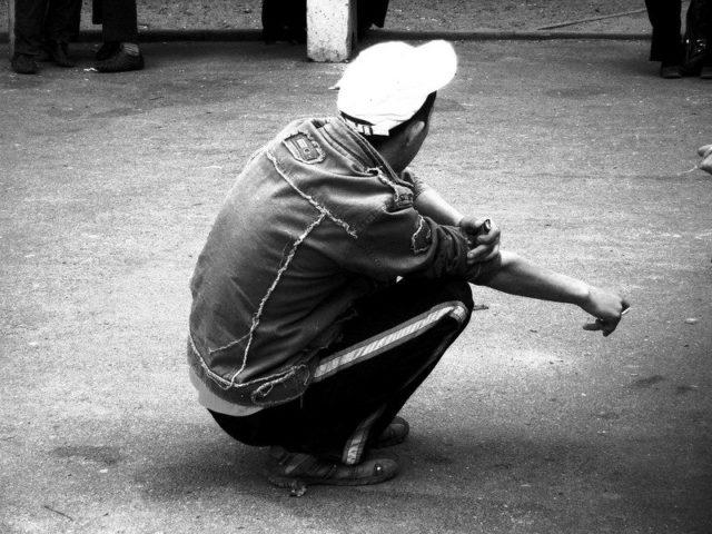 Молодой парень на корточках