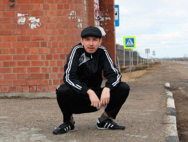 Мужчина сидит на корточках на остановке