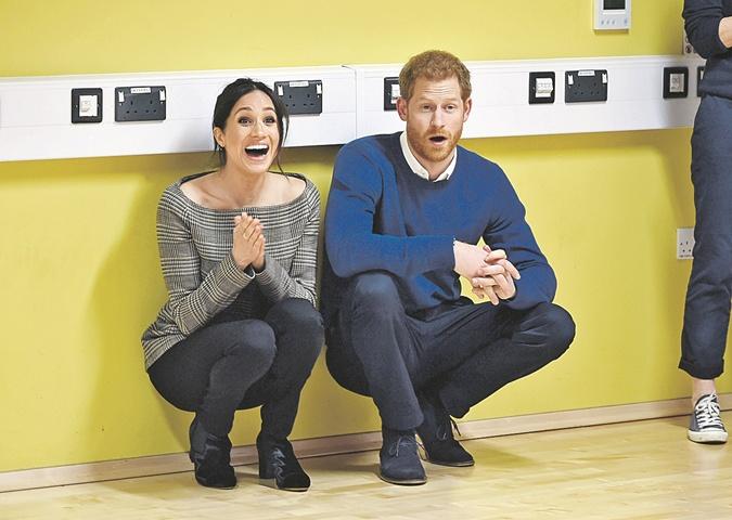 Меган Маркл и принц Гарри сидят на корточках