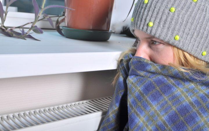 Девушка в одеяле возле батареи