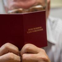 Мужчина держит пенсионное удостоверение