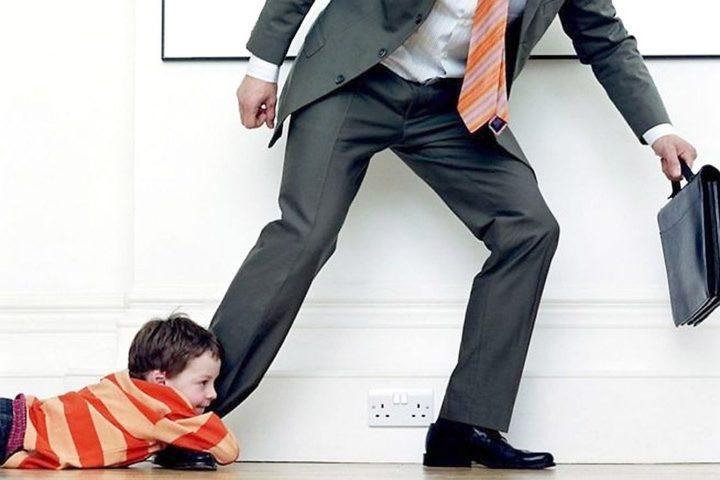 Мальчик держится за ногу мужчины