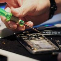 Мастер ремонтирует телефон