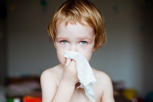Мальчик высмаркивает нос