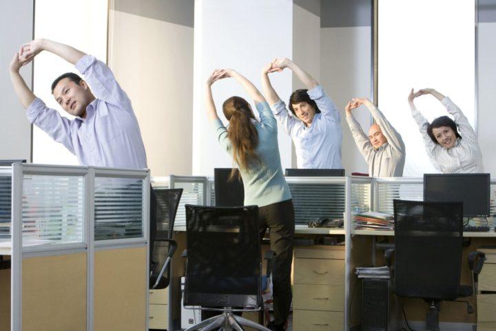 Сотрудники в офисе делают зарядку