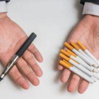 Мужчина держит в руках вейп и сигареты