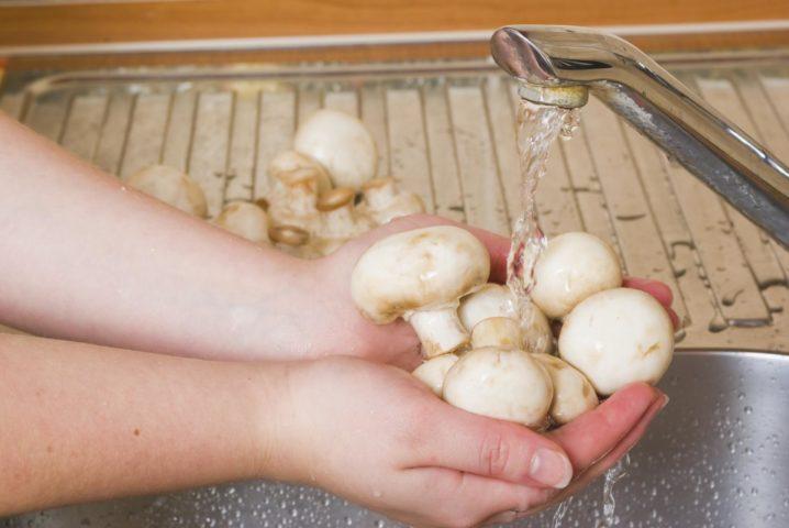 Девушка моет грибы