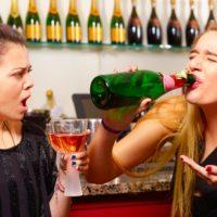 Девушка пьет из бутылки и кривится