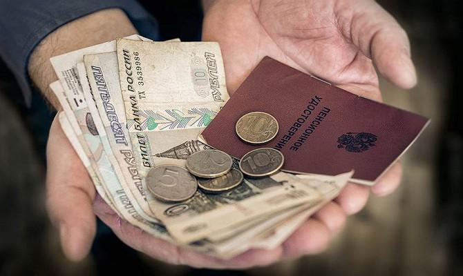 Деньги и пенсионное удостоверение в руках у пенсионера