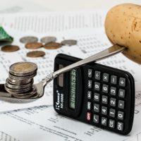 Ложка с монетами и картошкой на калькуляторе