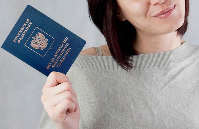 Девушка держит документ ВНЖ