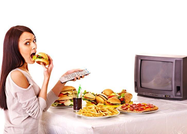 Девушка перед телевизором с едой