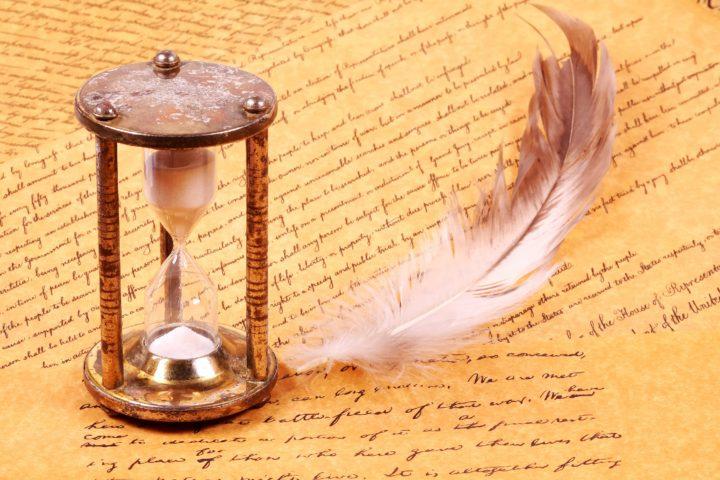 Песочные часы, перо и написанный на бумаге текст