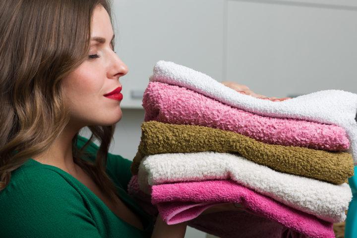 Девушка со стопкой махровых полотенец