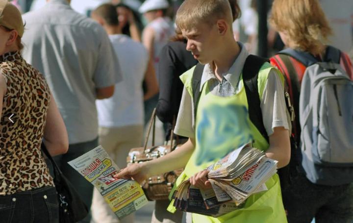 Подросток раздает флаеры