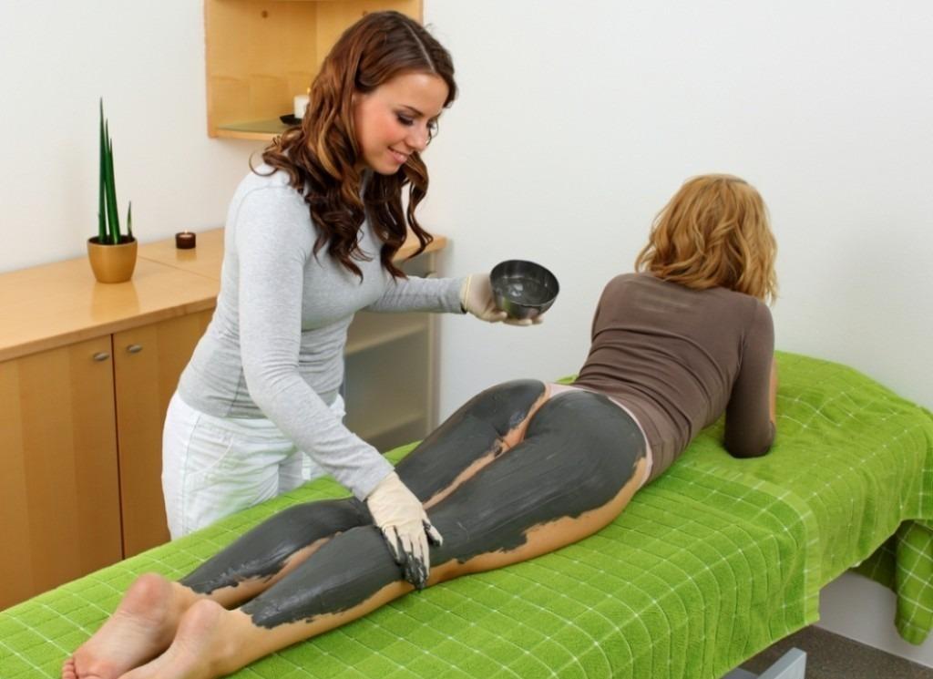 Косметолог наноси девушке маску на ноги