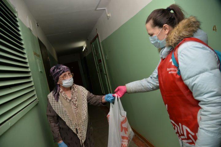 Волонтер передает пакет с продуктами пожилой женщине