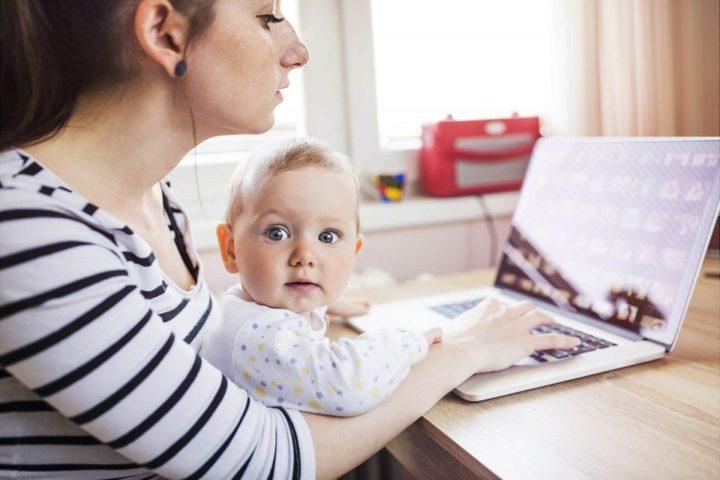 Женщина с ребенком на руках за ноутбуком
