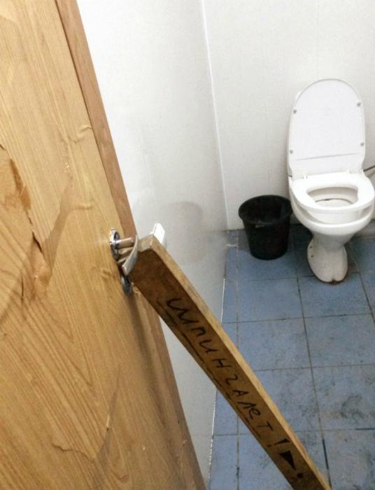 Дверь туалета, подпертая палкой