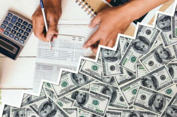 Доллары, счета, калькулятор, ручка в руках