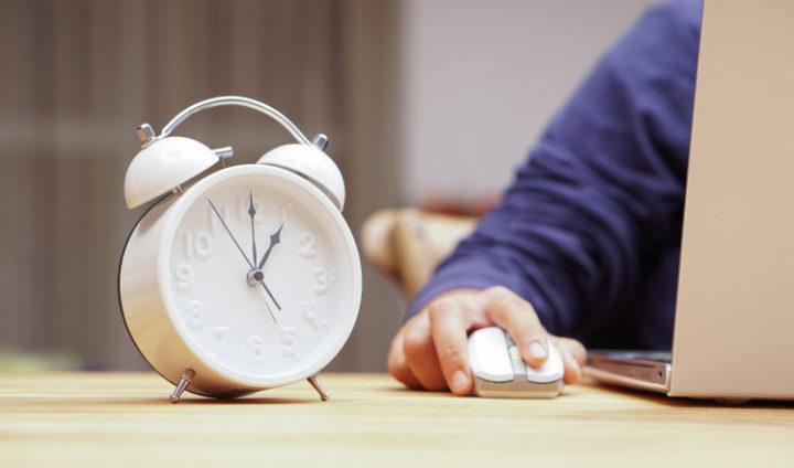 Часы на столе, муская рука на компьютерной мышке